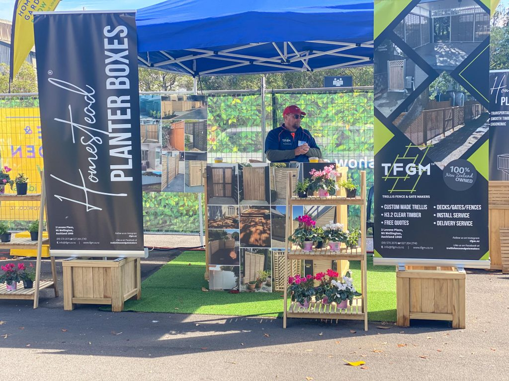 A stall featuring Trellis Homestead Planter boxes of various sizes and the sales representative.
